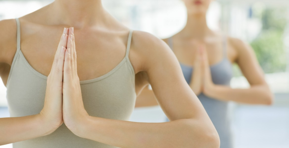 Two young women meditating with hands joined